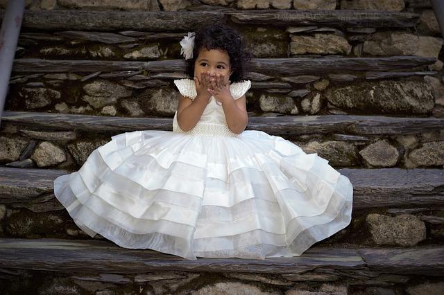 白いドレスを着て階段に座り口に手を当てている少女