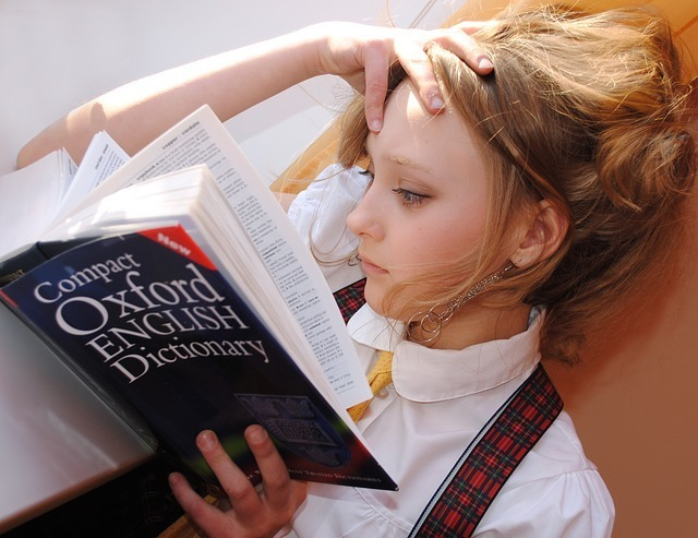 オックスフォード英英辞書を持って頭に手を当てる女性の写真
