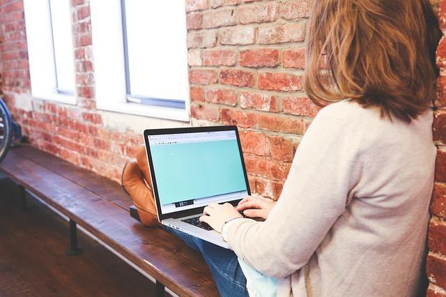 窓際に座ってパソコンで仕事をしている女性の写真
