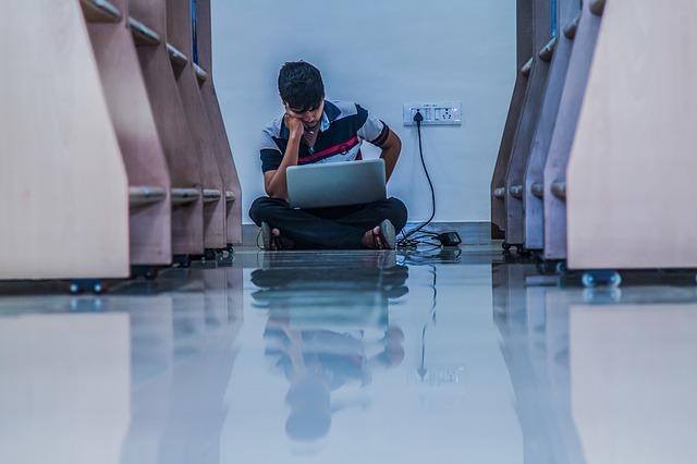 座り込んでパソコンをしている男性の写真