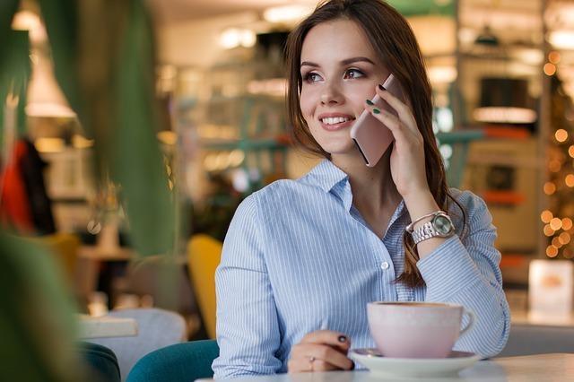 女性がカフェで電話をしている