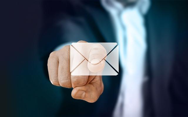 メールのアイコンを指で押している写真