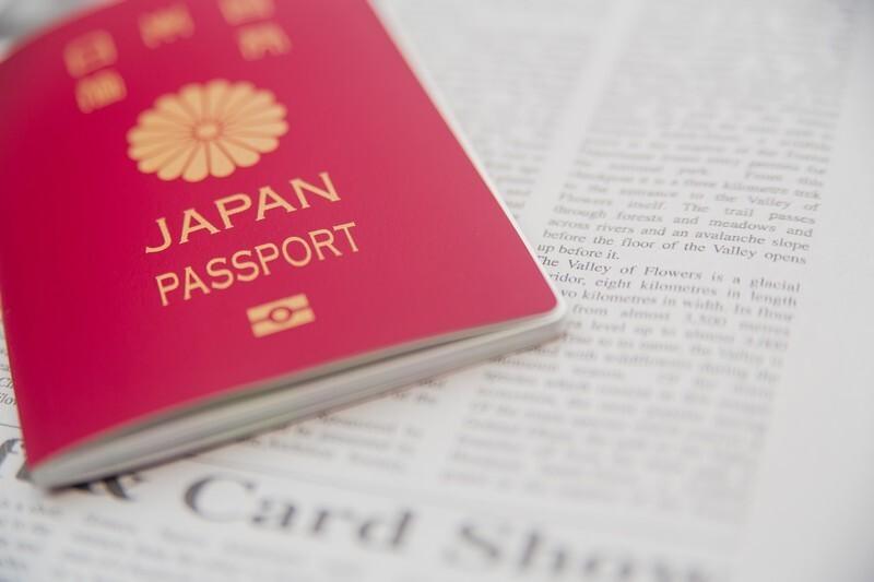 日本のパスポートと英字新聞の写真