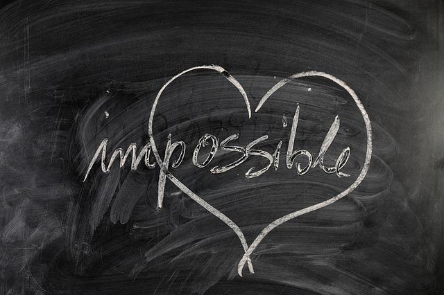 黒板に白チョークでかかれたimpossibleという文字とハートマークの写真