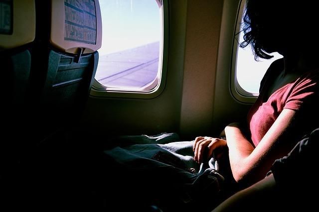 旅客機内の座席に座り窓外を見る女性の写真