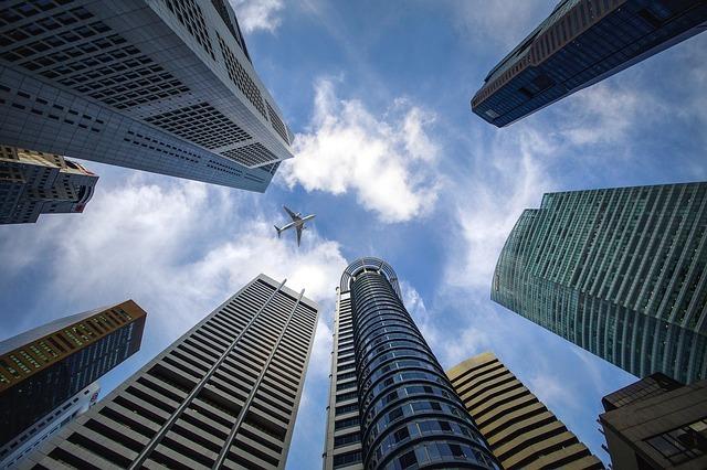 ビル群と空と飛行機を見上げる写真
