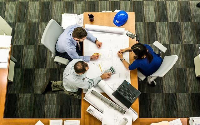 オフィスで3人の外国人がミーティングしている写真