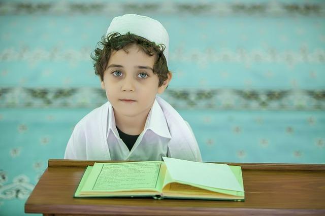 ノートを前に座っているイスラムの少年の写真
