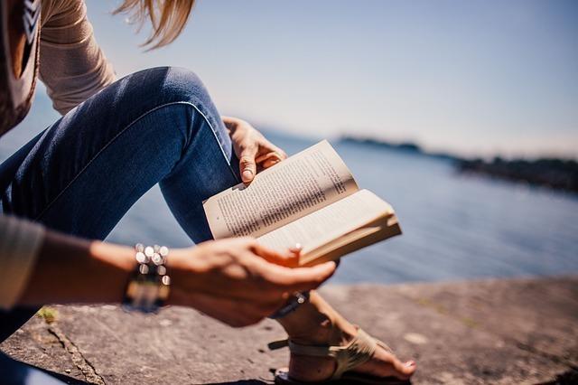 女性が水辺に座って本を読んでいる