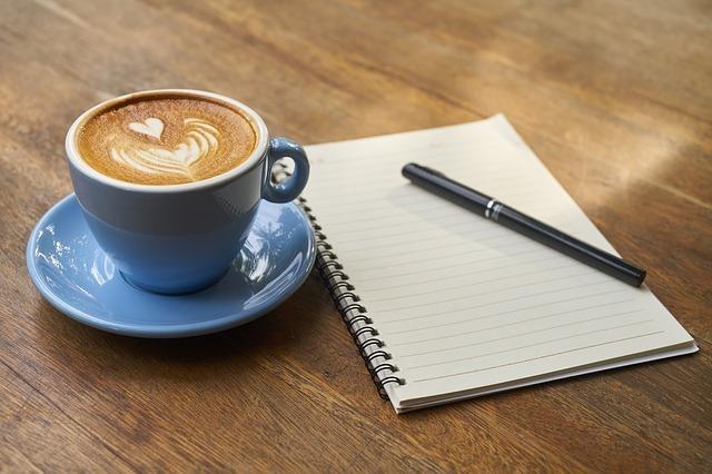 コーヒーとノートとペンが木製のテーブル上に置いてある