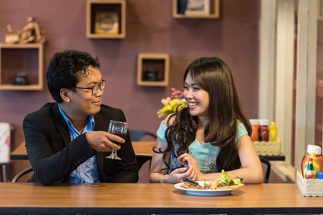 ワイングラスを持った男性とお皿を前にした女性が会話している写真