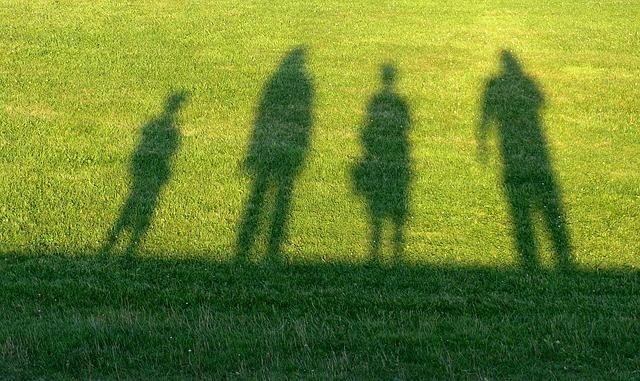 芝生上の4人の影の写真