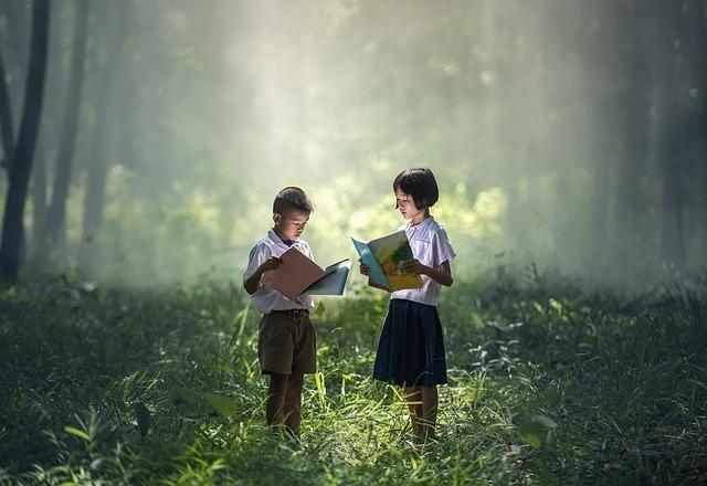 子供2人が森で本を読む写真