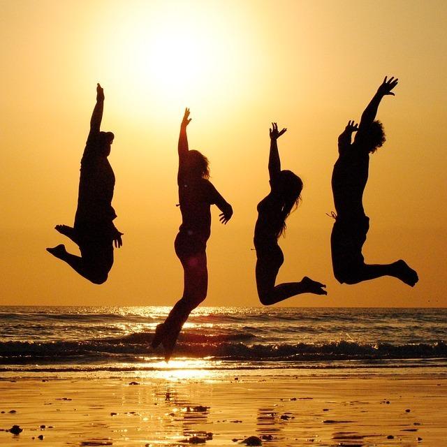 夕日をバックに、男女4人が浜辺でジャンプしている写真