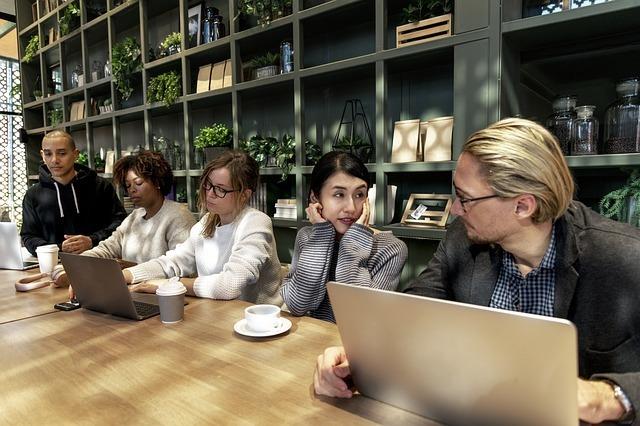 5名が並ぶオフィスで白人男性と話す日本人女性