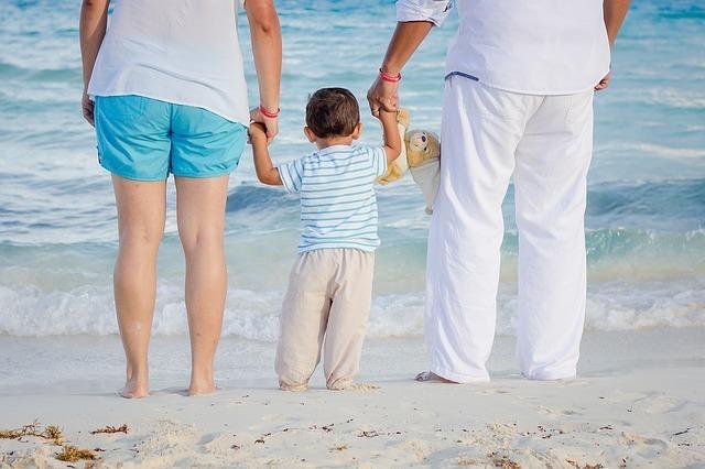 男性と女性の間で手をつなぐ子ども