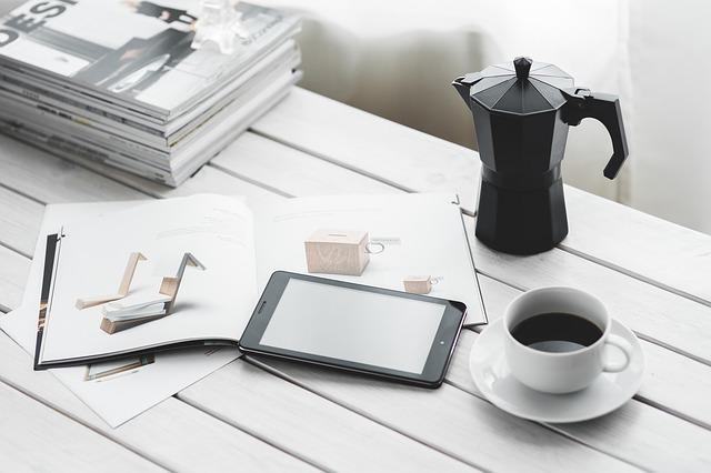 雑誌、タブレット、コーヒーの写真