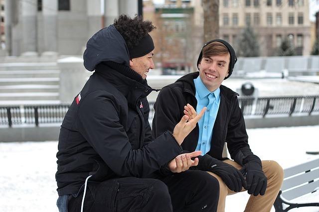 男性2人がベンチに座って話している写真です。