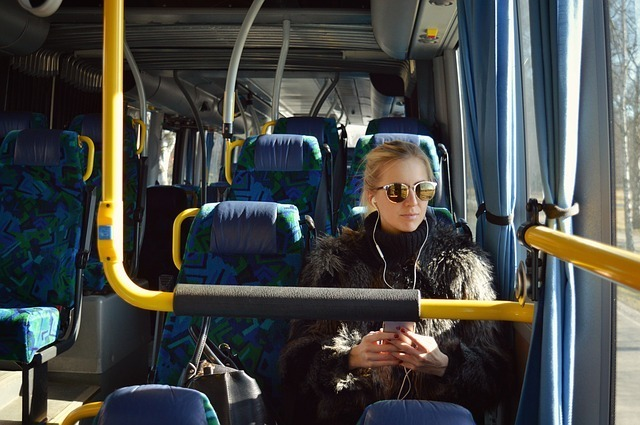 バスの中でスマートフォンを使って音楽を聴く女性