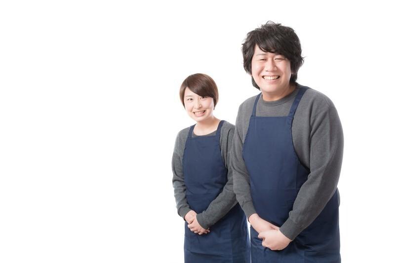 エプロンをつけた男性と女性が微笑んでいる写真
