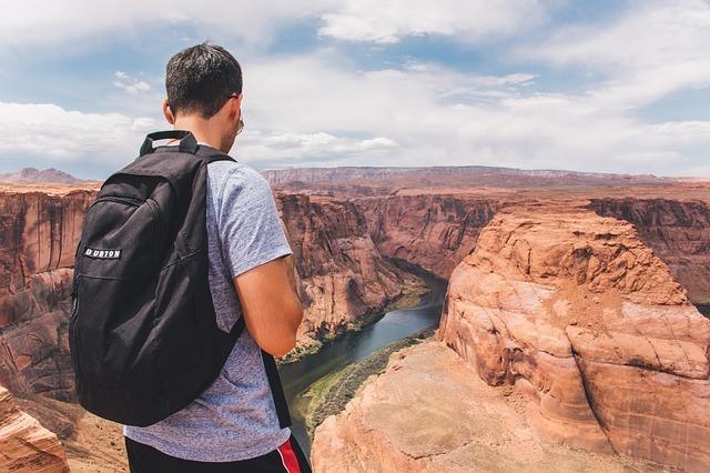 リュックを背負って崖の淵に立つ男性