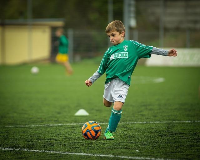 サッカーボールを蹴る緑の服を着た男の子の写真