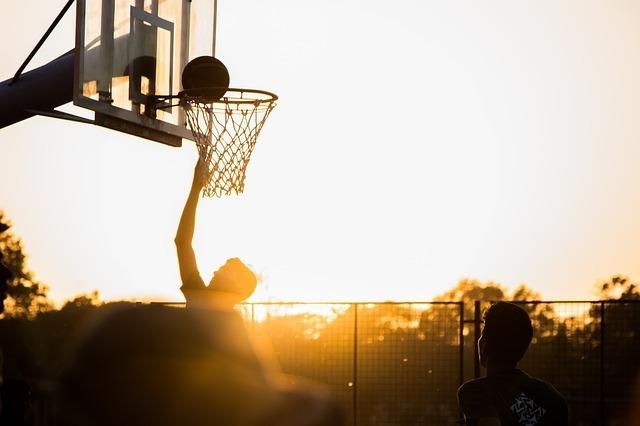 バスケットボールをシュートする男性のシルエットの写真