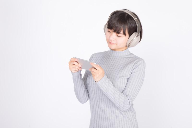 ヘッドフォンをつけた女性がスマートフォンを見ている写真