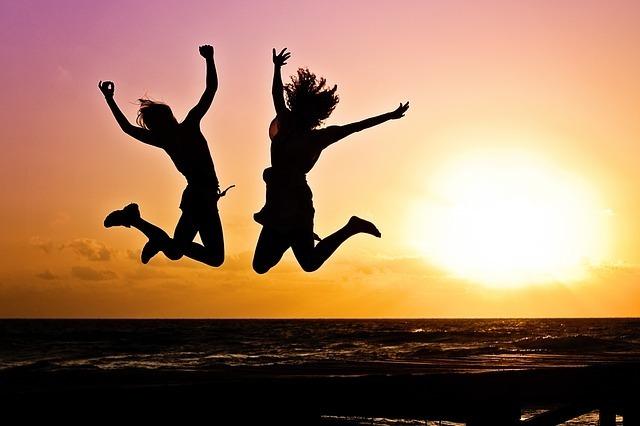 海で二人がジャンプしている画像