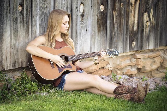 芝生の上で女性が座ってギターを引いている写真