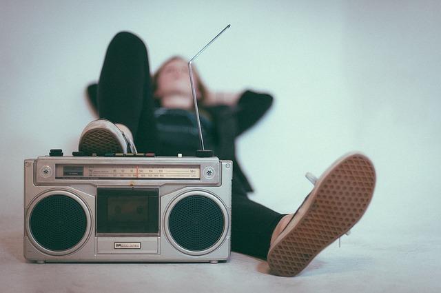 仰向けに寝た男性が右足をラジカセの上に置いている写真
