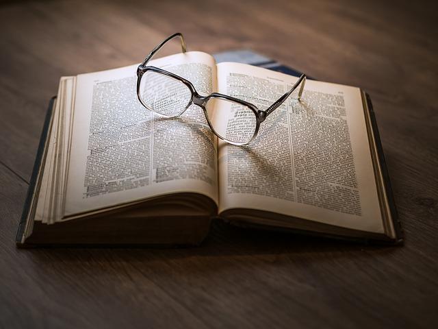 英語の古い本の上に黒縁メガネが乗っている写真
