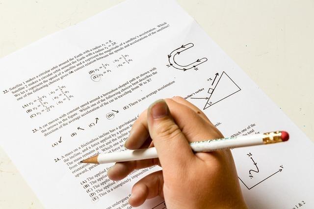 試験問題と鉛筆を持った手が写っている写真