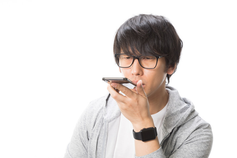 スマートフォンに声を吹込む男性