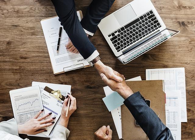 ビジネスパートナーと信頼関係が生まれ、握手する場面
