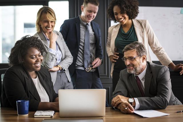 3人の女性と2人の男性がパソコンを見ながら談笑している写真