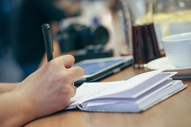 ノートにペンで何かを書く人間の手