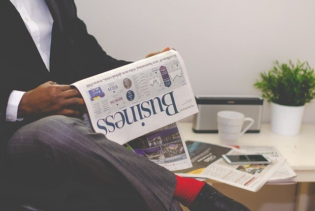 ビジネスマンが英字新聞を読んでいる