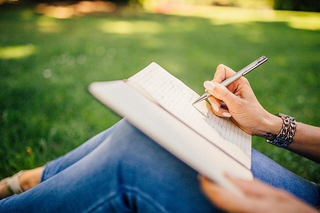 屋外で文章を書く人