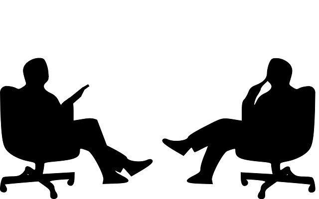 男性二人が椅子に座って向かい合って話しているシルエット