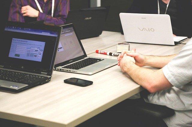 数人がパソコンを見ながら会話をしている