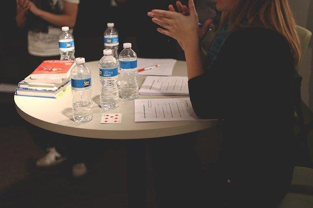 テーブルに水数本があり、女性がテーブルについている