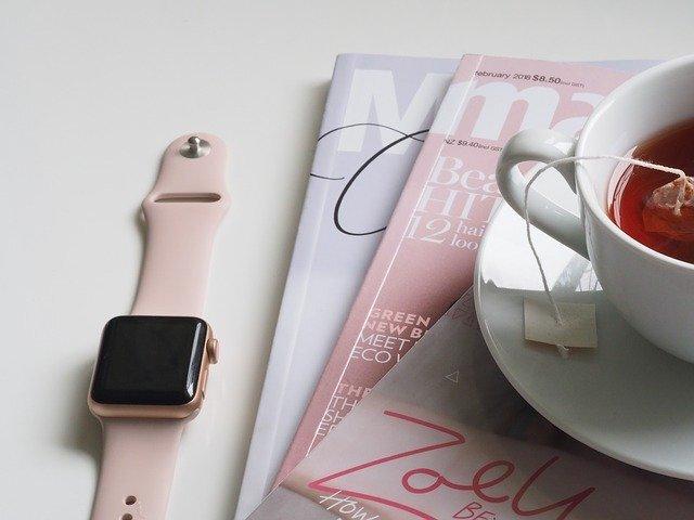 ピンク色のApple Watchと紅茶と雑誌