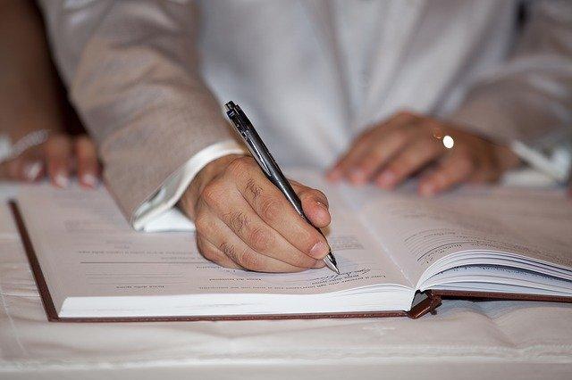 本にペンで文字を書く人