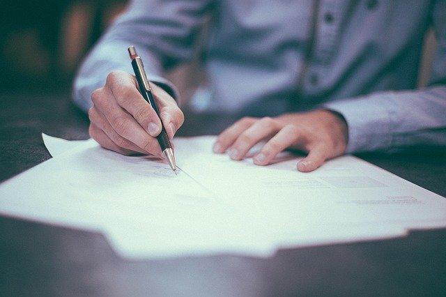 紙にペンで字を書いている人