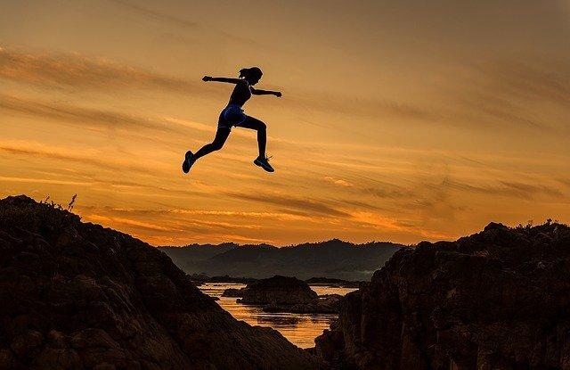 夕焼けの中ジャンプする女性