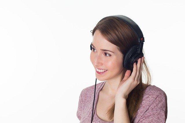 女性がヘッドフォンをつけて何かを聞いている