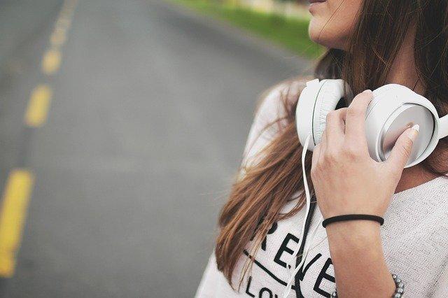 ヘッドフォンを首にかけた女性の写真